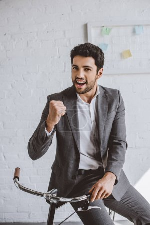 excited handsome businessman sitting on bike and showing yes gesture in office