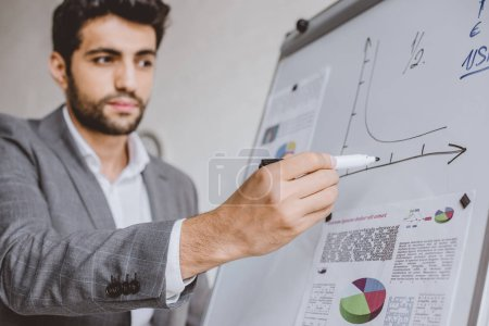 handsome businessman drawing chart on flipchart in office