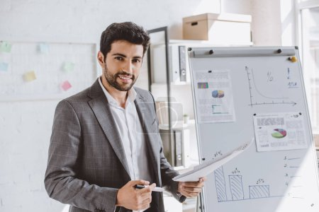 smiling handsome businessman presenting project on flipchart and looking at camera in office