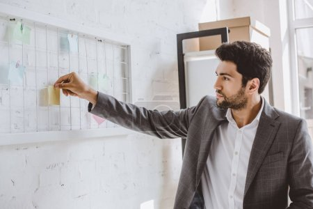 handsome businessman putting paper sticker on task board in office