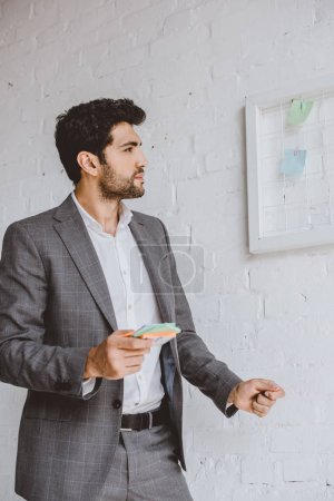 handsome businessman holding paper stickers and looking at task board in office