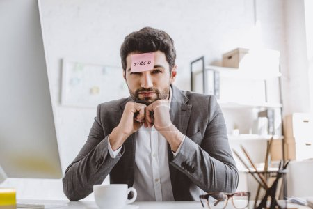 businessman sitting with paper sticker on forehead with word tired in office