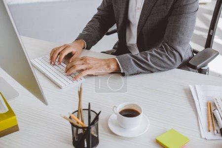 Photo pour Cropped image d'homme d'affaires en tapant sur le clavier de l'ordinateur de bureau - image libre de droit