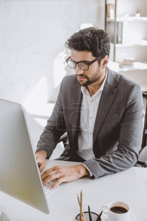 handsome businessman working at computer in office
