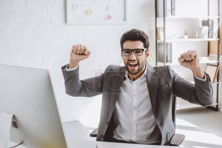 excited handsome businessman screaming and showing yes gesture in office