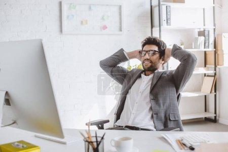 Photo pour Heureux homme d'affaires beau regardant l'ordinateur avec les mains derrière la tête au bureau - image libre de droit