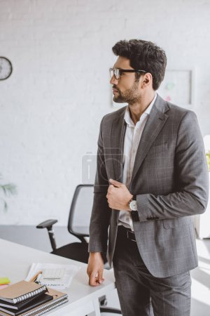 handsome businessman standing and looking away in office