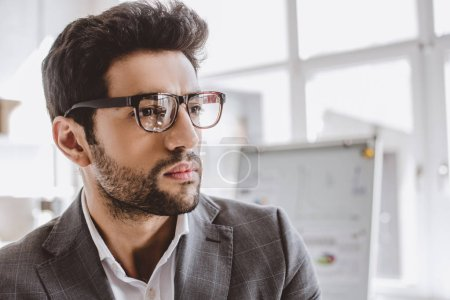 portrait of handsome businessman in glasses looking away in office