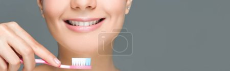 cropped shot of smiling woman holding tooth brush in hand isolated on grey
