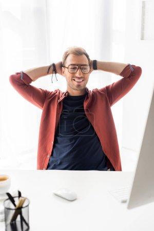 Photo pour Sourire d'homme d'affaires assis à table avec les mains derrière la tête - image libre de droit