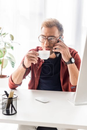 businessman drinking coffee while talking on smartphone in modern office