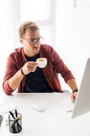 businessman in glasses holding cup of coffee in modern office