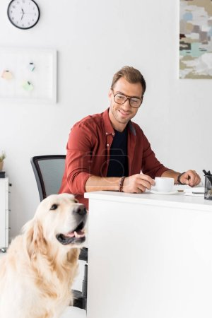 happy businessman with golden retriever dog in modern office