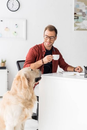 golden retriever sitting near businessman drinking coffee