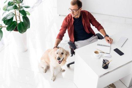 Photo pour Bel homme d'affaires et chien golden retriever au bureau moderne - image libre de droit