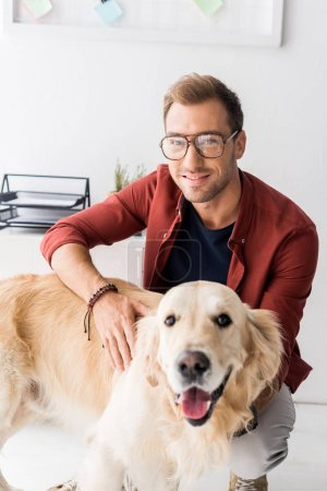 happy man in glasses stroking golden retriever dog