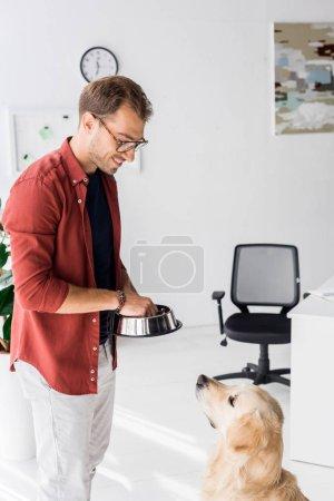 Man feeding cute dog with food from metal bowl