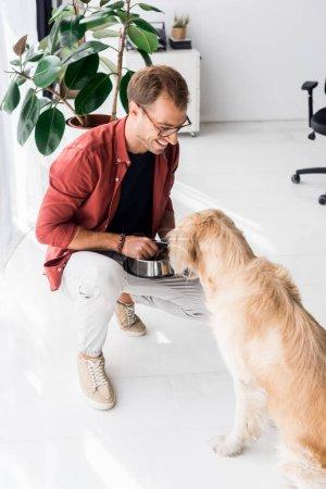 Man in glasses feeding golden retriever dog