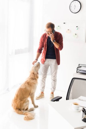 man talking on smartphone and stroking golden retriever dog