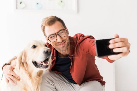 happy man taking selfie on smartphone with cute golden retriever dog