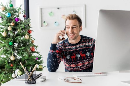 Photo for Businessman in christmas sweater talking on smartphone in modern office - Royalty Free Image