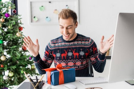 surprised businessman in winter sweater looking at christmas gift box