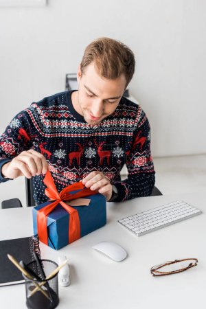 smiling businessman in christmas sweater opening gift box