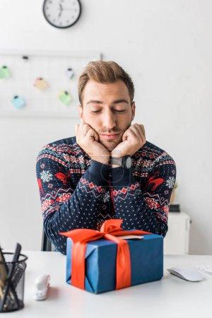 homme d'affaires bien pensé en pull de Noël en regardant sa boîte cadeau en bureau