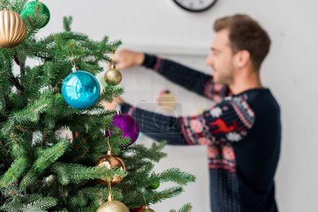 man in christmas sweater hanging christmas tree toys