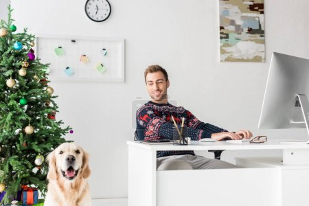 smiling man in christmas sweater sitting by table near golden retriever dog