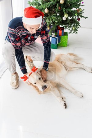man in christmas sweater and santa hat stroking golden retriever dog