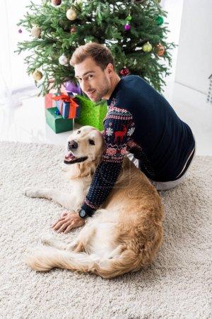 man in christmas sweater sitting near golden retriever dog