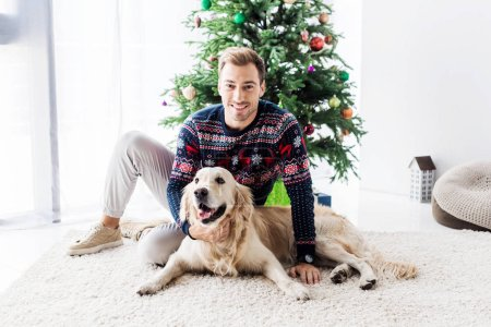happy man in sweater with golden retriever dog sitting near christmas tree