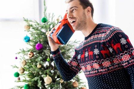 homme au pull de Noël avec coffret près de la tête contre l'arbre de Noël