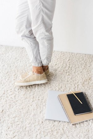 Low section view of casual man and laptop on beige rug