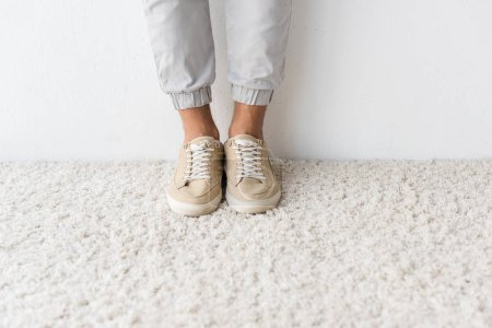 Low section view of fashionable man on beige rug