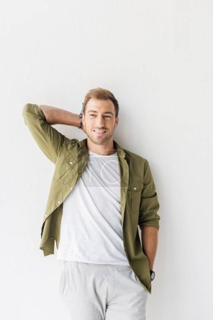 smiling man in green shirt against white wall