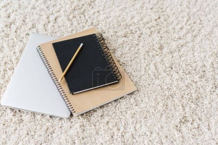 elevated view of laptop and notebooks on beige rug