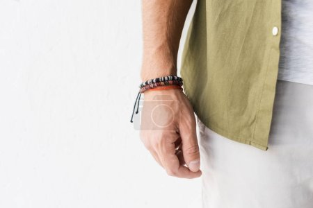 cropped view of male hand with bracelets against white wall