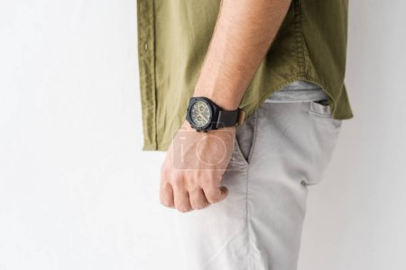cropped view of male hand with wristwatch against white wall