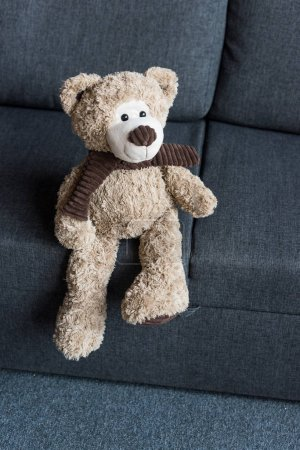 high angle view of cute brown teddy bear on grey couch