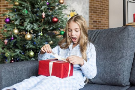 surprised child in pajamas opening christmas gift while sitting on couch