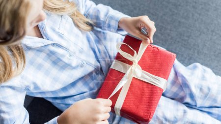 cropped shot of child in pajamas opening gift box