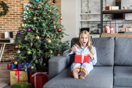 surprised child in pajamas opening christmas gift and looking at camera