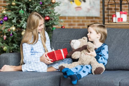 cute happy kids in pajamas holding teddy bear and christmas present while sitting in sofa and smiling each other
