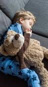 high angle view of adorable child sleeping on sofa with teddy bear