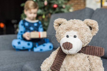 close-up view of teddy bear and child holding christmas present behind