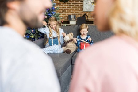 selective focus of parents on foreground and happy kids in pajamas opening christmas presents