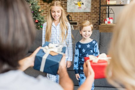 selective focus of parents presenting christmas gifts to happy children in pajamas