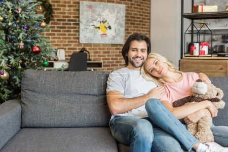 Photo for Beautiful happy young couple sitting together on sofa and smiling at camera at christmas eve - Royalty Free Image